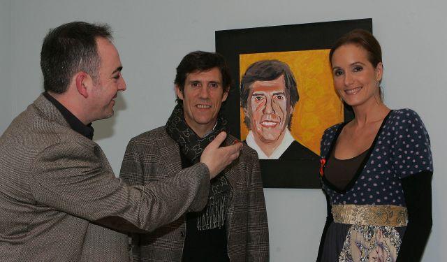 Javier Moro posa con Sandra Ibarra ante su retrato en la exposición Rostros solidarios